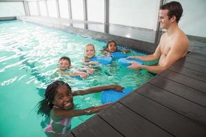 linda clase de natación en piscina con entrenador foto
