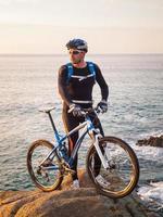 Ciclista de bicicleta de montaña con paisaje marino en el fondo foto