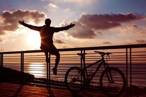 silueta de deportista y bicicleta de montaña al atardecer foto