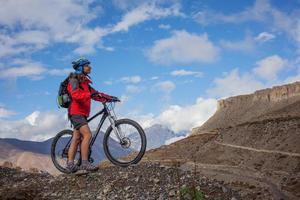Chica en bicicleta en la carretera en el Himalaya foto