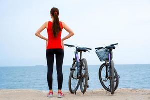 mujer deporte con bicicletas en la playa foto