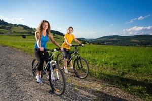 Two women riding bike