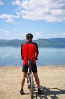 man with bike on a mountain lake photo