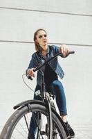 Young woman hipster standing with black bike