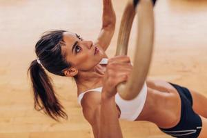 Young fit woman pulling up on gymnastic rings