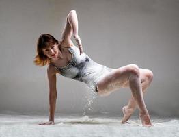 Hermosa bailarina de ballet expresivo posando con harina en el estudio