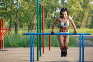 Sporty girl doing push ups on bars outdoor photo