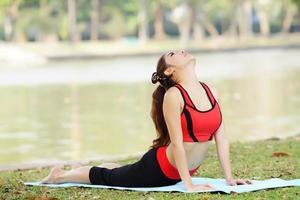joven mujer bonita haciendo ejercicios de yoga en el parque foto