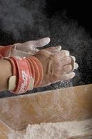 gimnasta masculino pulverizando las manos, primer plano de las manos foto