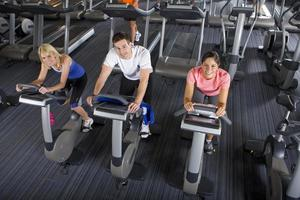 man and women riding exercise bikes in health club photo