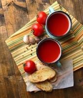 jugo de tomate casero en taza de color, tostadas y tomates frescos