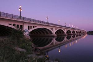 A bridge reflected in water at dawn