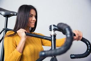 Woman holding bicycle on shoulder photo