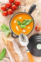 Tomato soup in a black casserole, drizzled with cream