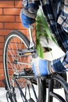 cerrar en la mano del hombre reparando una bicicleta foto