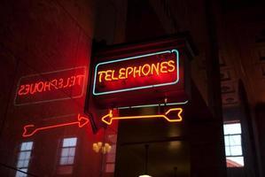 Neon Sign pointing toward public telephones photo