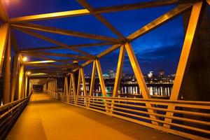 Floating crosswalk metal structures along river Willamette night lighting Portland