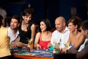 Riendo amigos jugando a las cartas en un casino foto