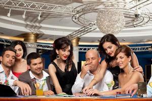 felices amigos caucásicos jugando blackjack en casino foto