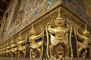 Ornate golden garuda figures adorning temple