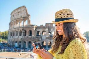 Woman checking photos near colosseum in rome, italy