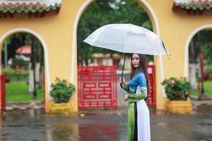 Las mujeres vietnamitas visten ao dai con paraguas bajo la lluvia foto