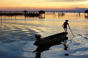 silueta de pescadores con sol amarillo y naranja