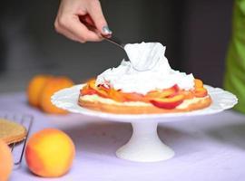mujer mano poner crema batida en pastel de durazno foto