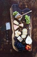 Wine appetizers set: French cheese selection, honeycomb, grapes, peach and photo