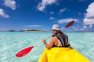 jovem homem caucasiano de caiaque no mar nas Maldivas