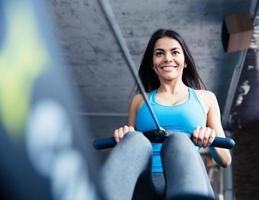 Happy charming woman working out at gym photo