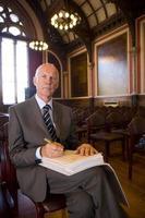 Senior male registrar preparing to sign document, portrait photo
