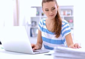 Frau mit Dokumenten, die auf dem Schreibtisch sitzen