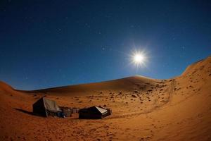 Camp in Sahara Desert night with moon and moving star