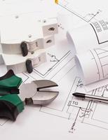 attrezzi da lavoro, miccia elettrica e rotoli di schemi su disegno