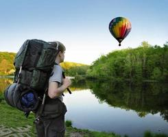 Backpacking hiker encounters a hot air balloon floating above a lake photo