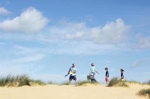 família andando duna de areia na praia
