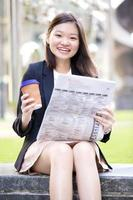 Young female Asian executive holding file