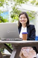 Young female Asian business executive using laptop