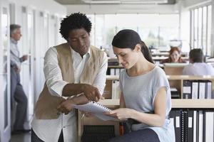 Empresario y colega discutiendo papeleo en la oficina