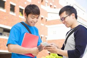 two students using a cell phone  to discuss photo