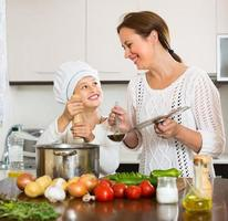 Mother and daughter cooking together photo