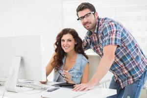 Smiling partners using computer together photo