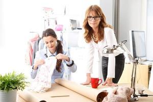 hermosos diseñadores de moda trabajando juntos en el estudio. foto
