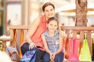 madre e hija sentadas juntas en el asiento del centro comercial