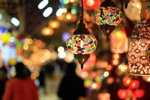 Bright, colorful lamps hung against blurred background photo
