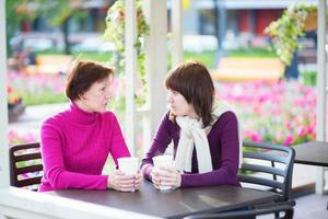 Mother and daughter together in cafe photo