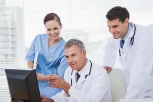 médicos y cirujanos trabajando juntos en la computadora foto