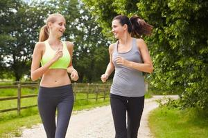 Two Female Friends On Run In Countryside Together