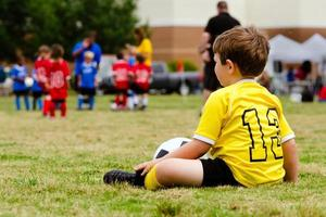 Child in uniform watching organized youth soccer